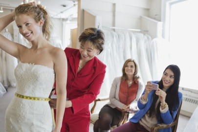Woman tailor measuring woman in wedding dress at bridal store