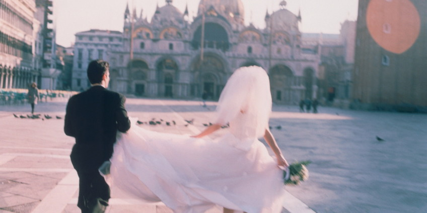 Italy, Venice, St Marks, bride and groom running